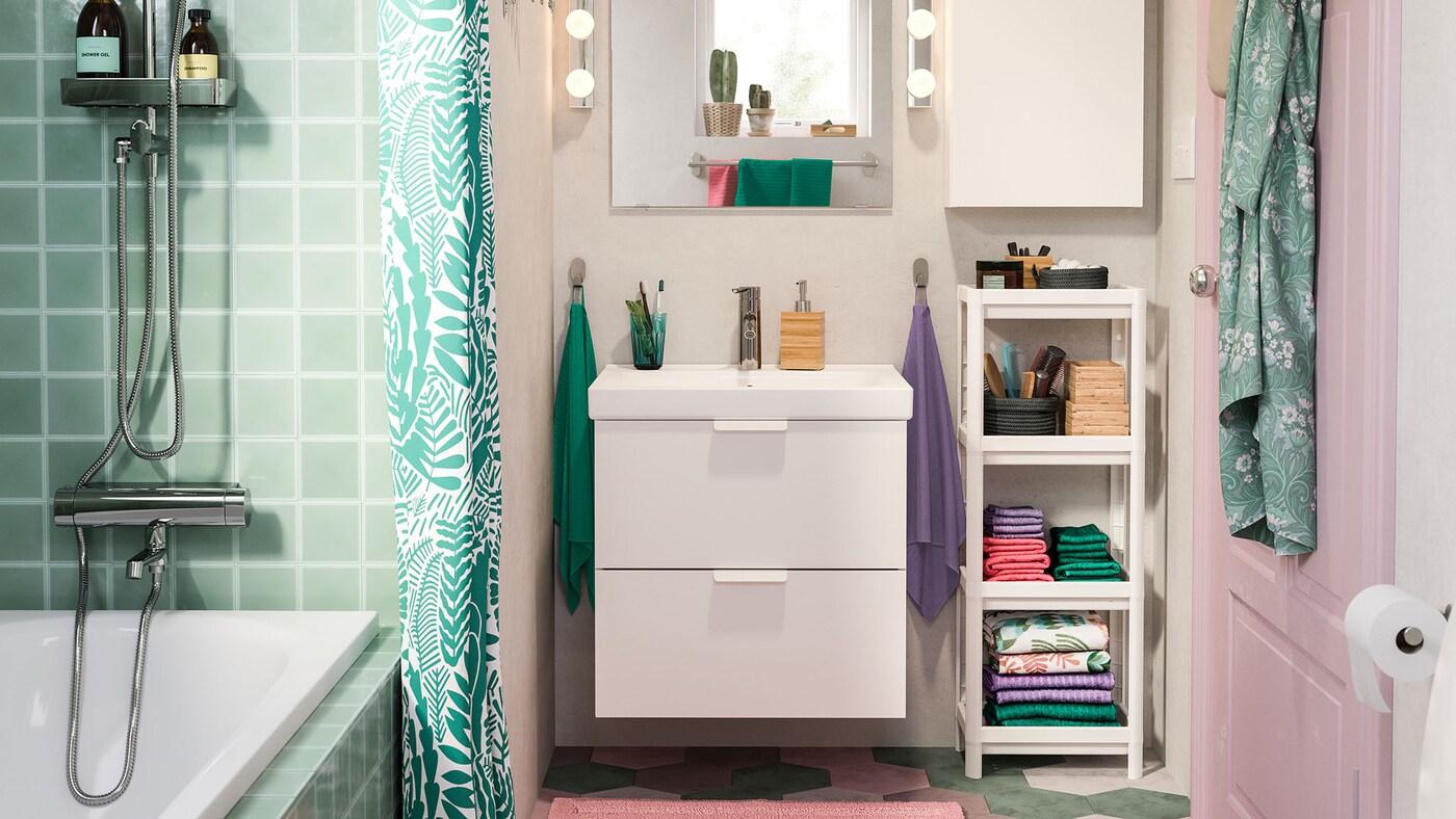 et badeværelse med blå klinker og et blå badekar og med et hvidt GODMORGON badeværelsesskab