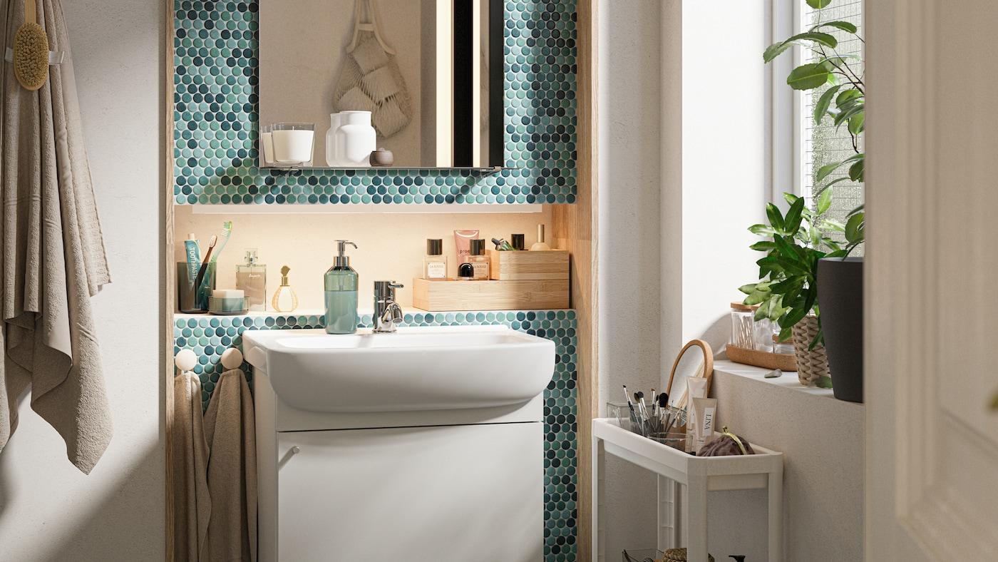 Et badeværelse med grønne fliser med et hvidt skab med vask, et spejl med hylde og et hvidt rullebord med toiletartikler.