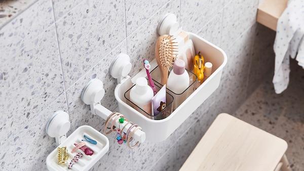 Et badeværelse med hvide, lyseblå og mintgrønne fliser og forskelligt badeværelsestilbehør.