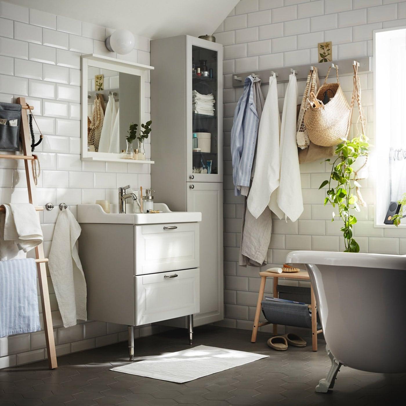 Et badeværelse med lysegrå låger i traditionel stil.