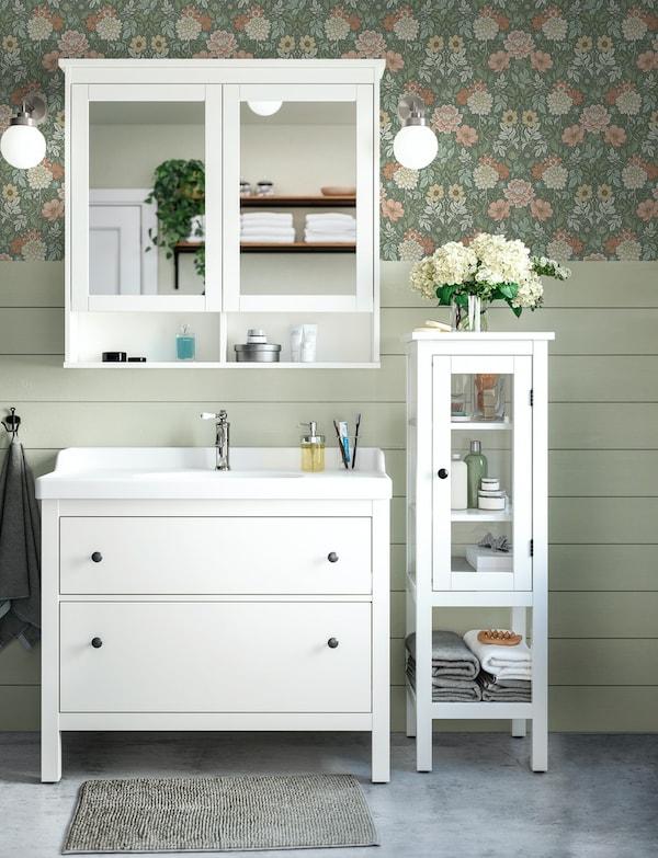 Et badeværelsessæt i klassisk stil, hvidt træ og med blomsteret tapet på væggene.