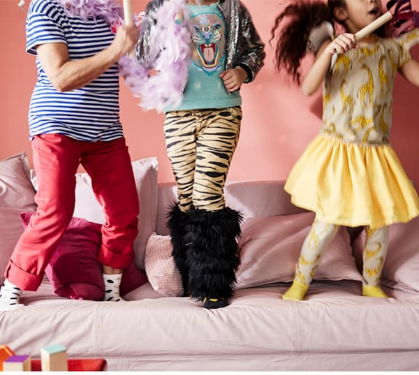 Et beskåret billede viser benene af 3 små børn, der leger sammen i en lyserød sofa.