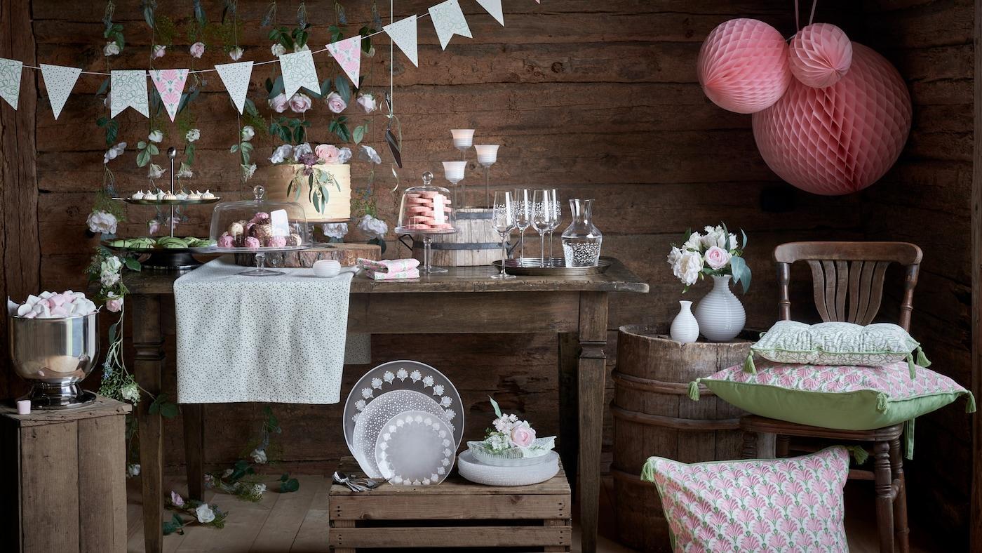 Et bord i en låve dekket til fest med glass, servise og dekorasjoner fra INBJUDEN-kolleksjonen.