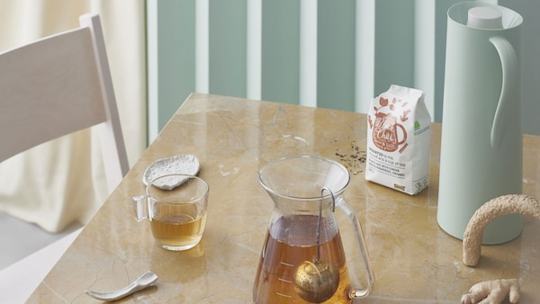 Et bord med tekopper og tekanne og teen EGENTID.