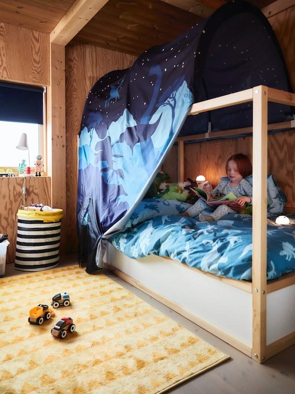 Et børneværelse med en seng med en blå sengehimmel. Der er dinosaurer på det blå sengetøj og tæppet på gulvet er gult. En dreng sidder og læser i sengen.