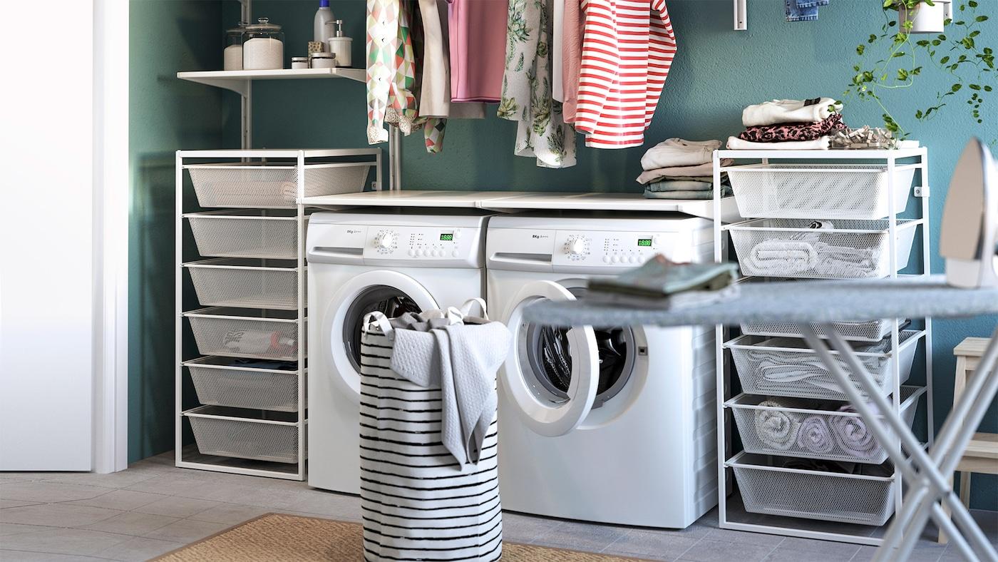 Et bryggers med vaskemaskine, tørretumbler, opbevaring i trådkurve, strygebræt og vasketøjskurv.