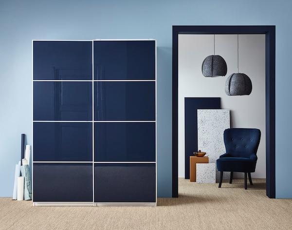 Et garderobeskab med blå skydedøre i moderne stil står i et soveværelse.