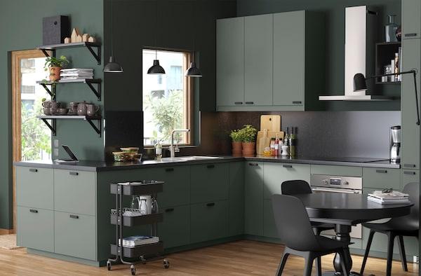 Et grågrønt køkken med hvidevarer og spiseplads til familien.