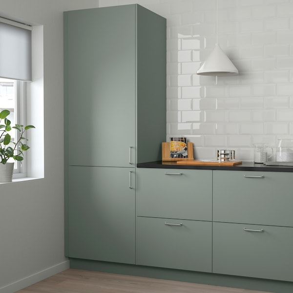 Et grågrønt køkken med sort bordplade og skærebræt.