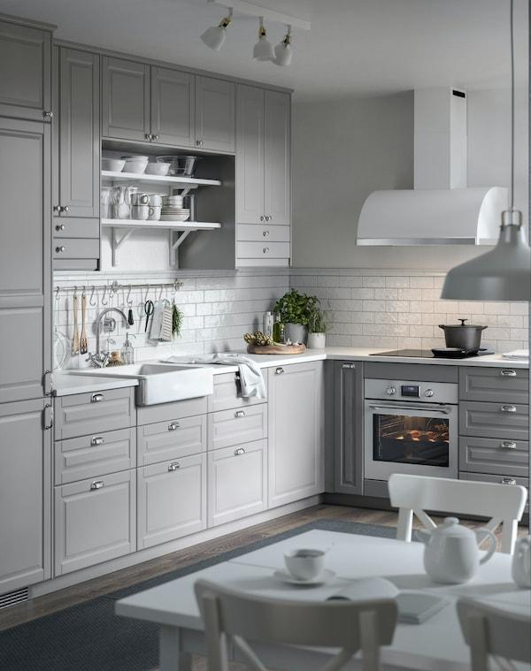 Et gråt, klassisk køkken med hvide metrofliser på væggen.