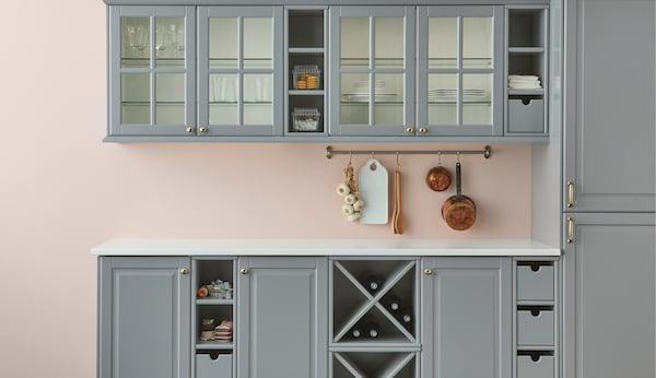 Et gråt traditionelt køkken med lyserød væg.