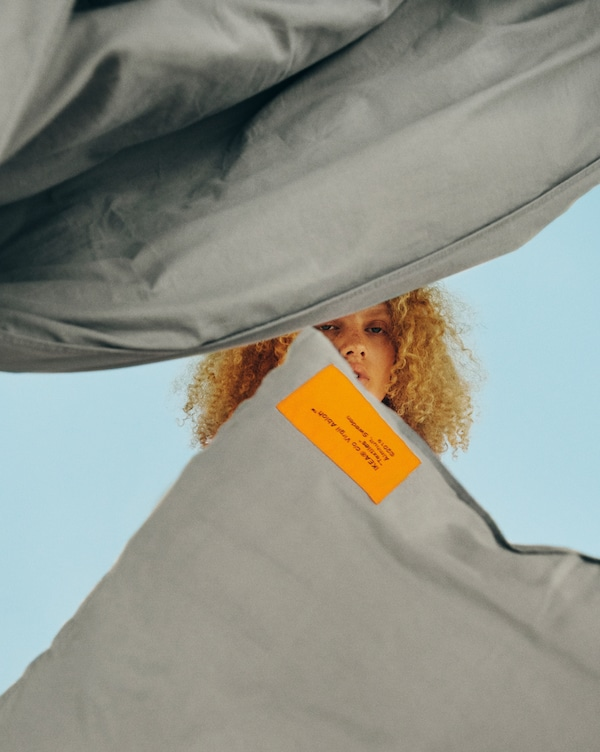 Et grått sengesett med et brodert oransje merke hengende i lufta som dekker ansiktet til en modell.