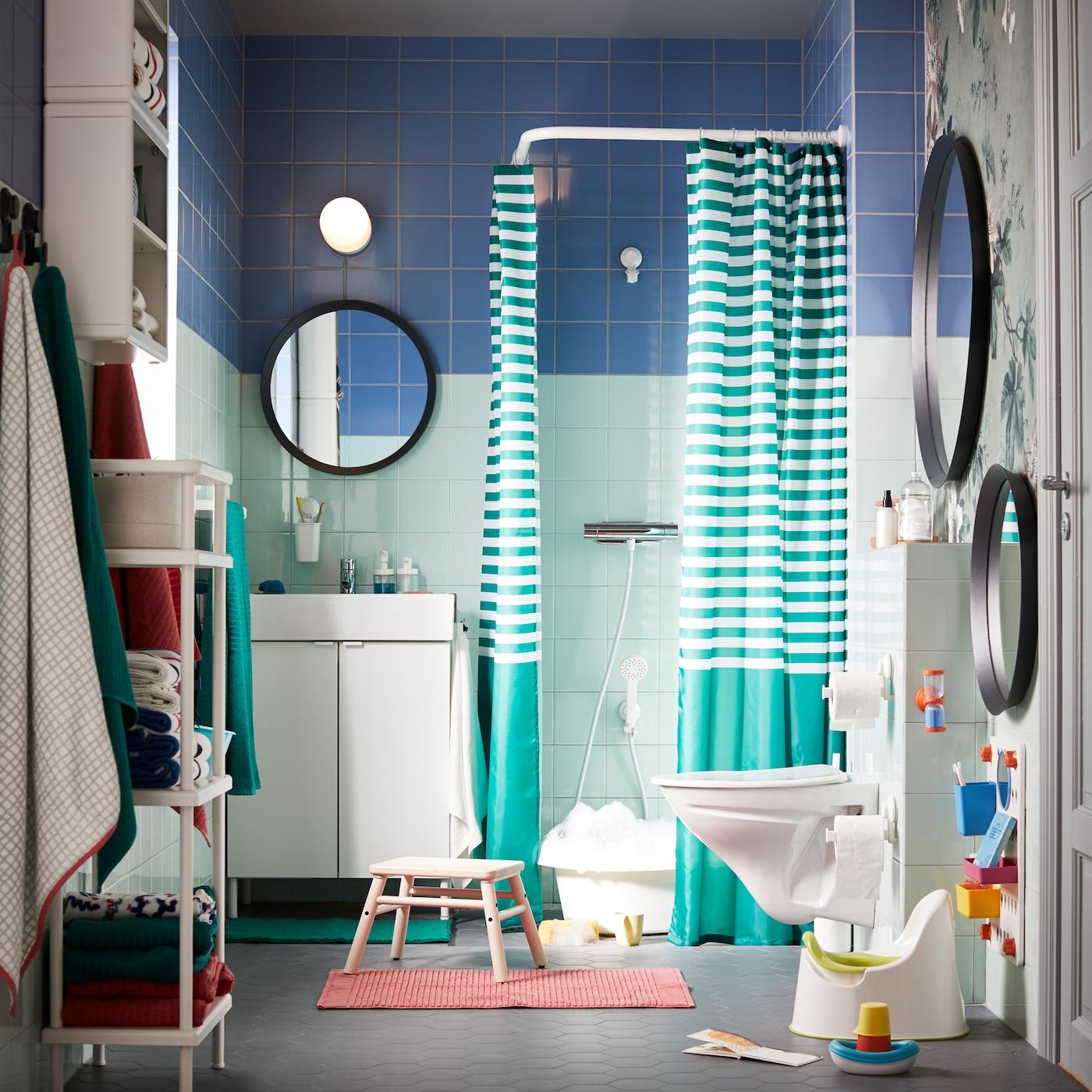 Et grønt/blåt badeværelse med farverigt og hvidt tilbehør og masser af opbevaringsplads, som kan tilpasses – til både voksne og små børn.