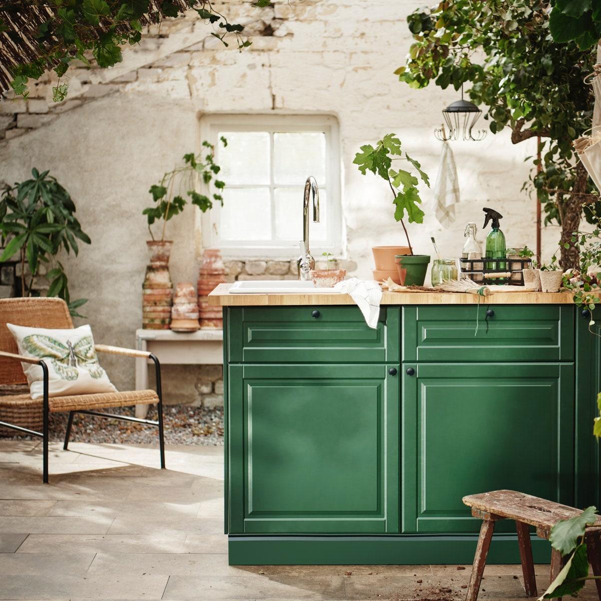 Et grønt køkken i et lyst rum.