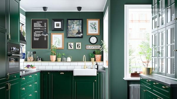 Et grønt køkken med en hvid vask med en synlig front, en messingfarvet hane, en gaskomfur og to sorte loftslamper.