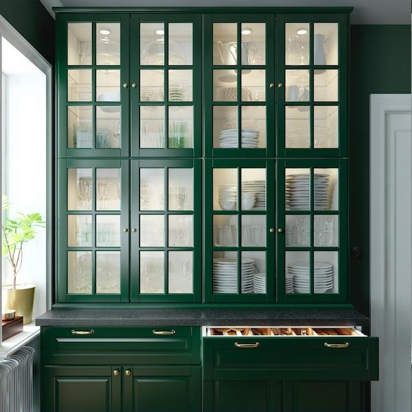 Et grønt vitrineskab skabt af virtrinelåger og køkkenhøjskabe.
