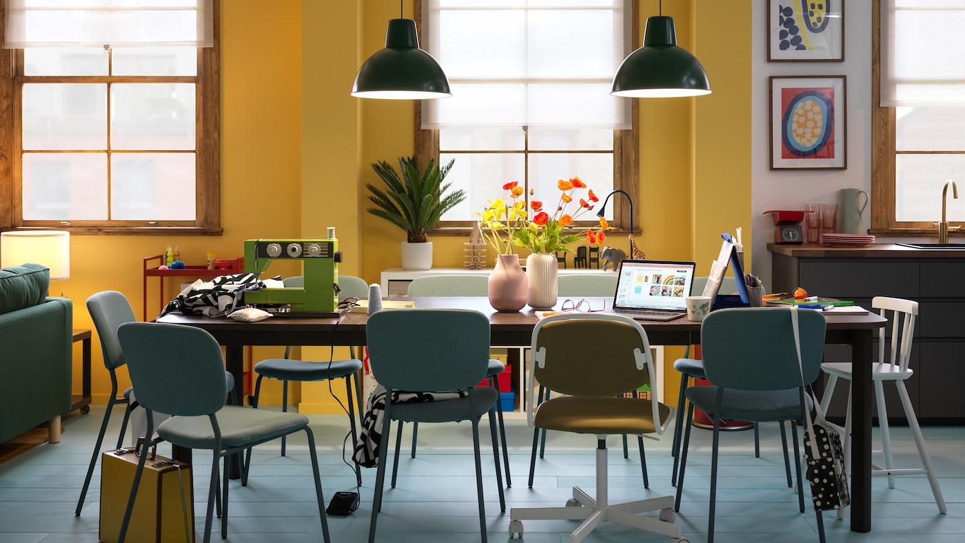 Et gult rum med et mørkebrunt STRANDTORP udtræksbord med forskellige slags stole omkring.