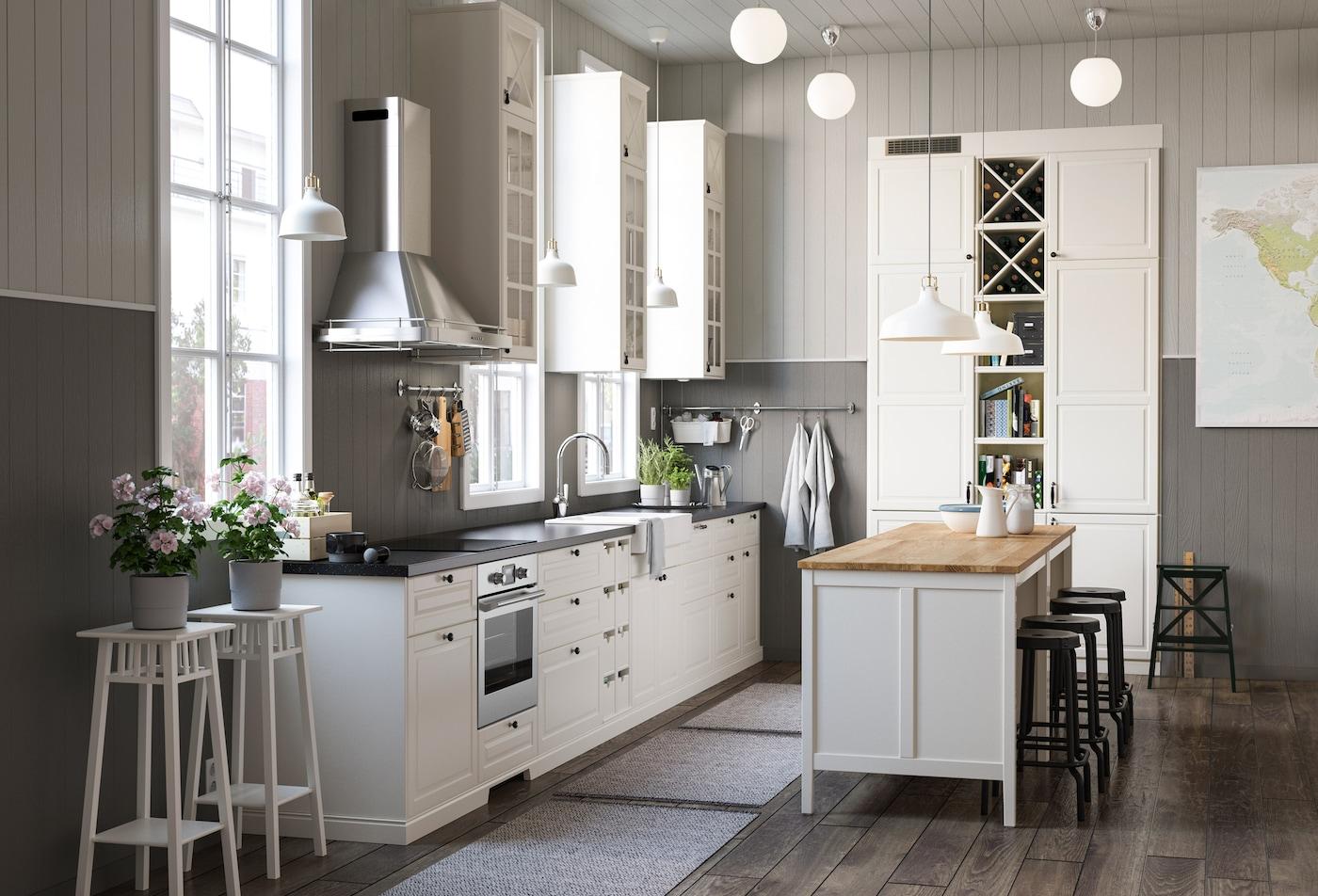 Et hjørne køkken med BODBYN råhvid døre og skuffefronter og vitrinedøre.