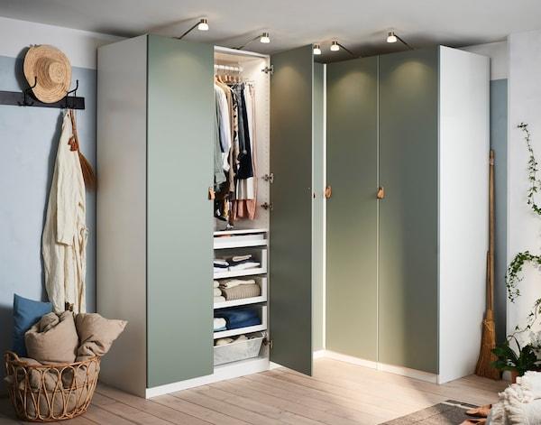 Et hjørnegarderobeskab med grå-grønne låger i et soveværelse.