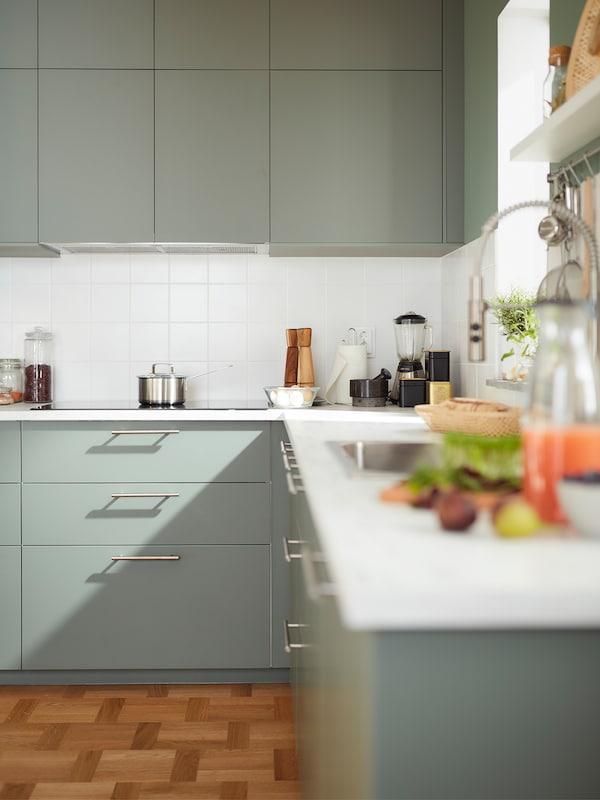 Et hjørnekøkken med grågrønne skabe, et komfur og en lysegrå mineraleffekt-bordplade med redskaber og apparater på toppen.