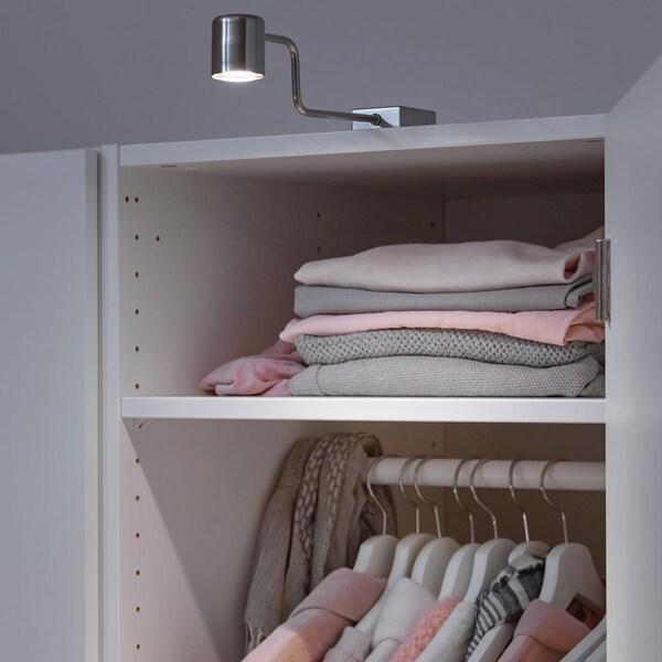 Et hvidt garderobeskab med en grå lampe ovenpå.