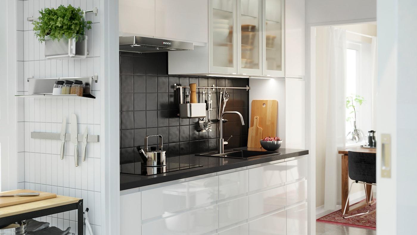Et hvidt køkken med hvide højglans fronter og glaslåger. Bordpladen er med sort mineralmønster.