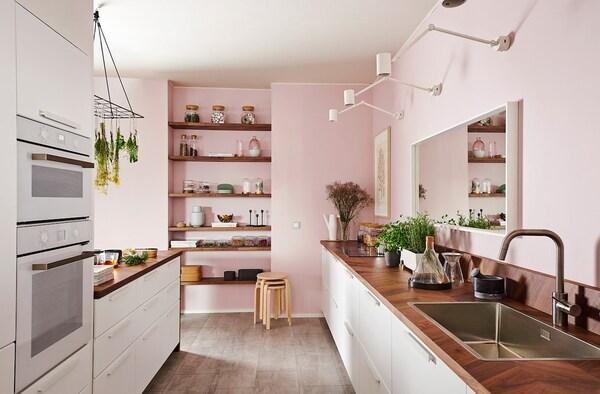 Et hvidt KUNGSBACKA køkken med køkkenø og lyserødt tema.