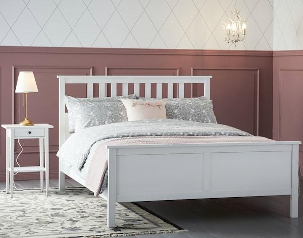 Et hvidt sengestel af træ står i et lyst soveværelse med høje, gammelrosa paneler.