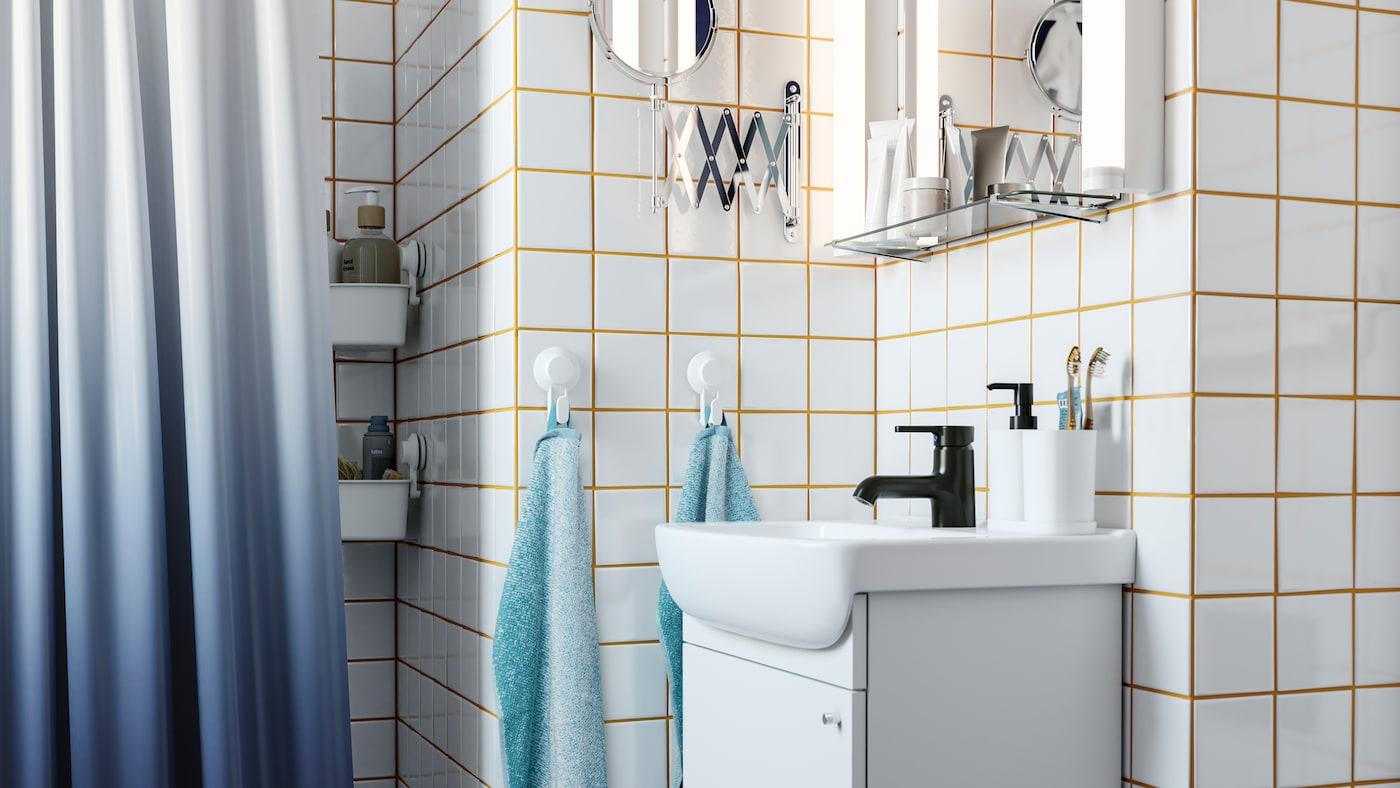 Et hvidt skab med vask, et sort blandingsbatteri, hvide fliser med gul fuge, et mørkeblåt badeforhæng og kroge med håndklæder.