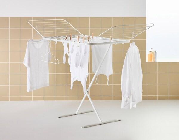 Et hvidt tørrestativ, der er foldet ud, står på et badeværelse med lysebrune fliser. Der hænger hvidt tøj til tørre på stativet.