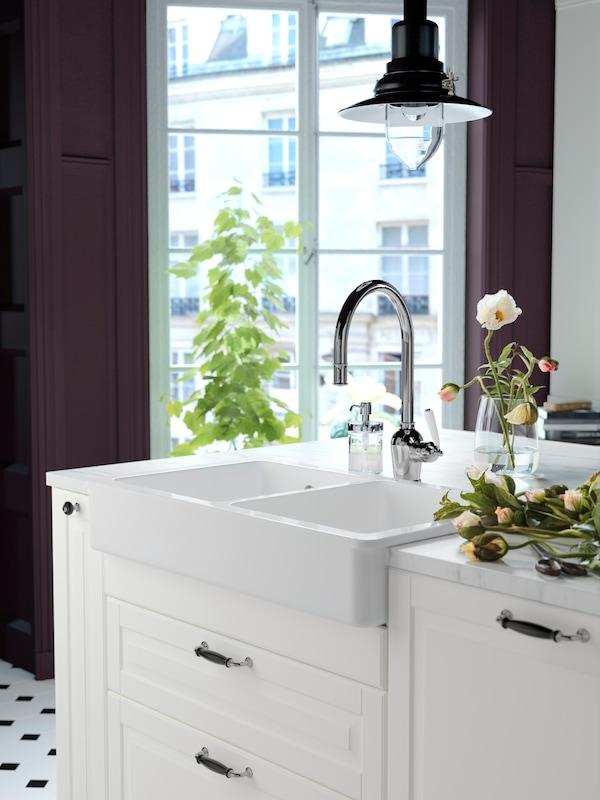 Et hvidt tradtionelt køkkenskab med dobbeltvask og blandingsbatteri.