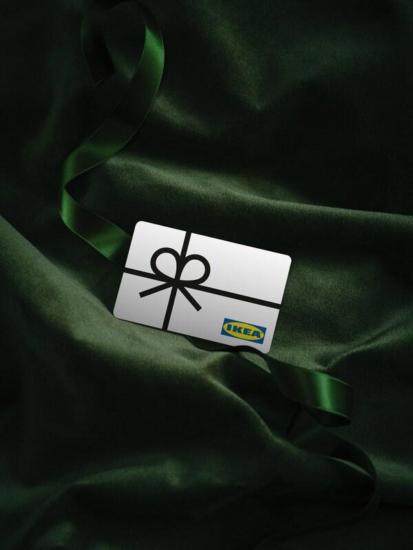 Et IKEA gavekort der ligger på grønt, glat stof.