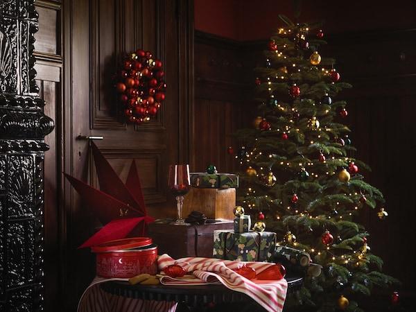 Et juletræ med pynt og lys står ved siden af et bord med julegaver og julegodter
