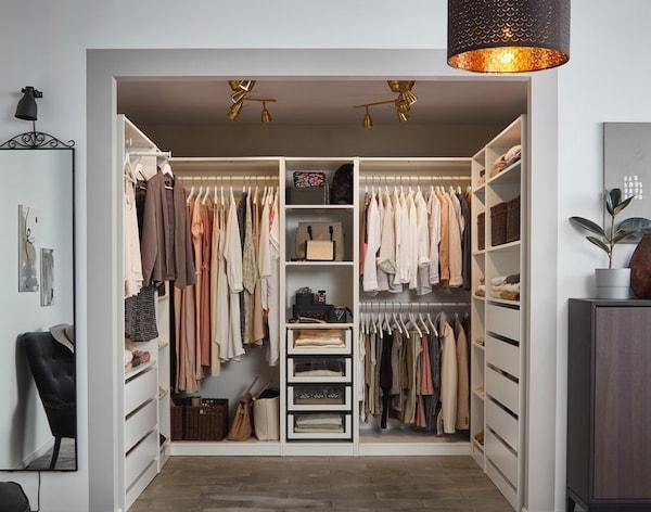 Et kig ind i en åben garderobeløsning, der fungerer som et walk in closet.