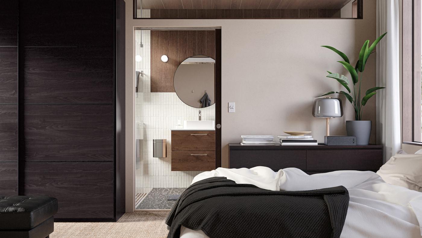 Et kig ind i et elegant badeværelse fra en dør i et soveværelse. På badeværelset er der et skab af træ med vask, et rundt spejl og beige fliser.