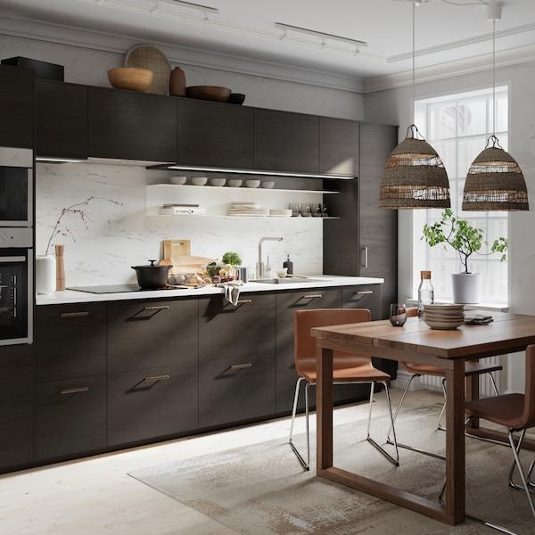 Et kjøkken med fronter i mørkebrunt askemønster og veggplate i hvitt marmormønster, spisebord i tre og skinnstoler.
