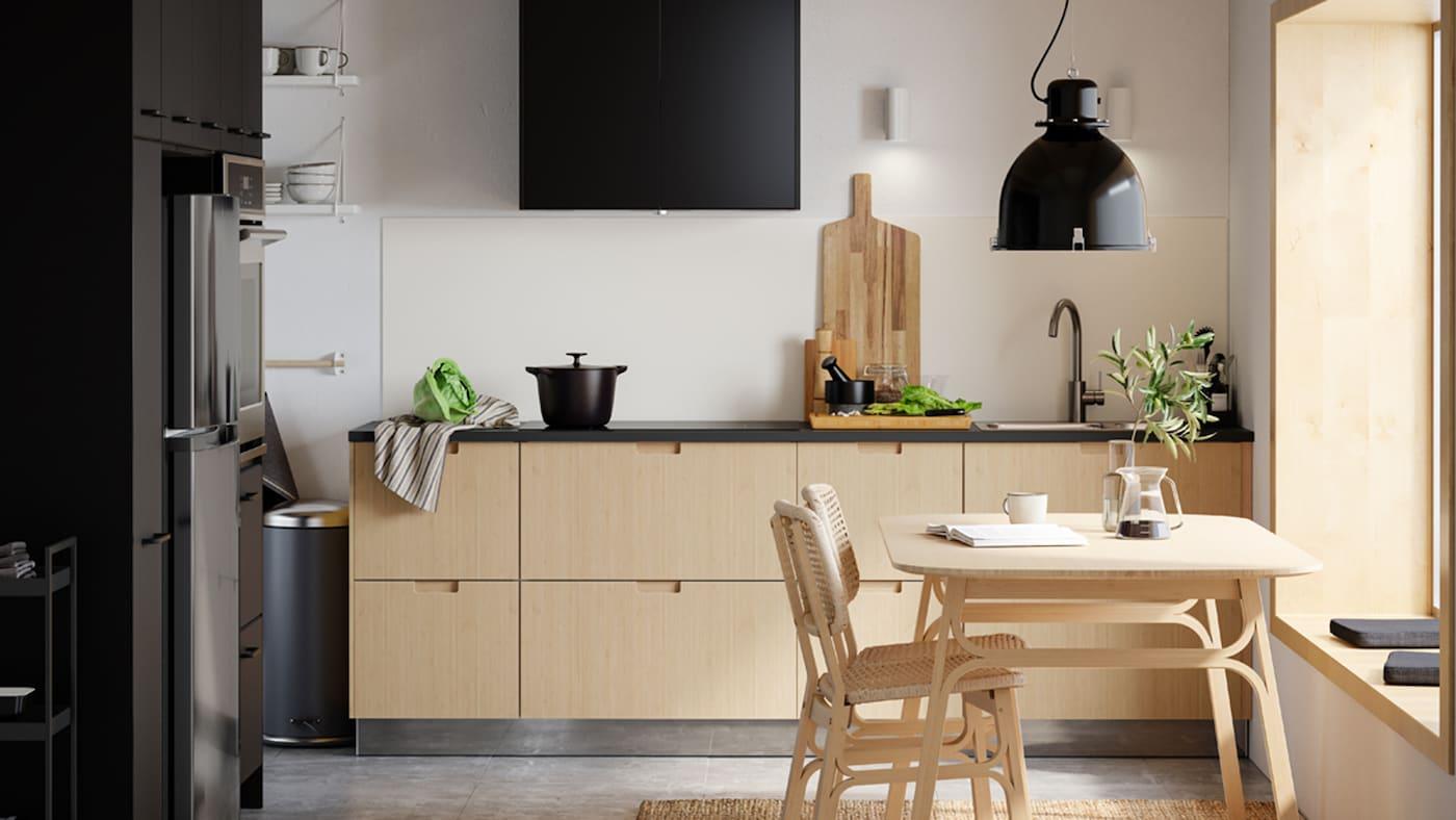 Et køkken i traditionel stil med hvide låger. Vægskabene har vitrinelåger med sprosser. Midt i rummet er en spisesplads med et bord og seks sorte stole.
