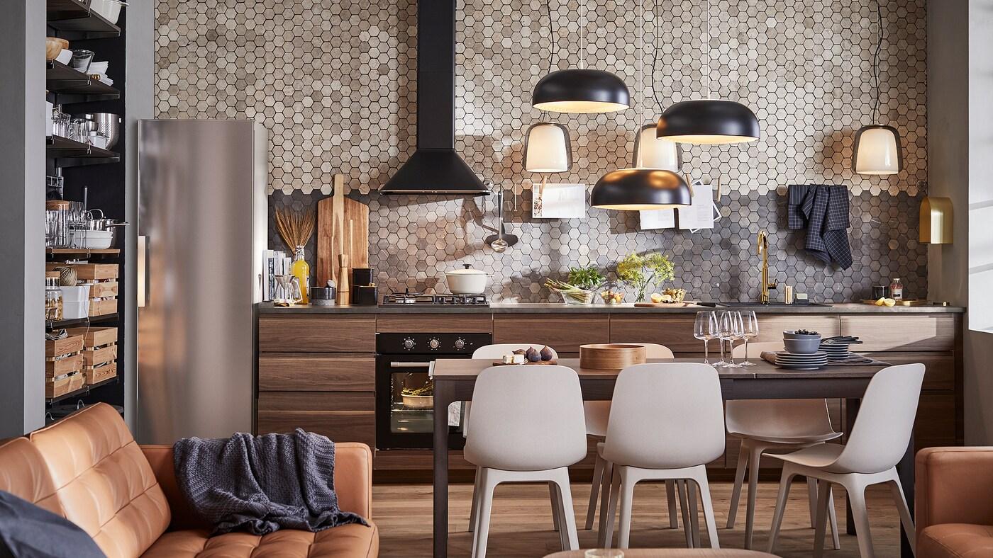 Et køkken med skabe i mørkebrunt valnød-træ, tre sorte pendellamper, et mørkebrunt bord og seks stole.