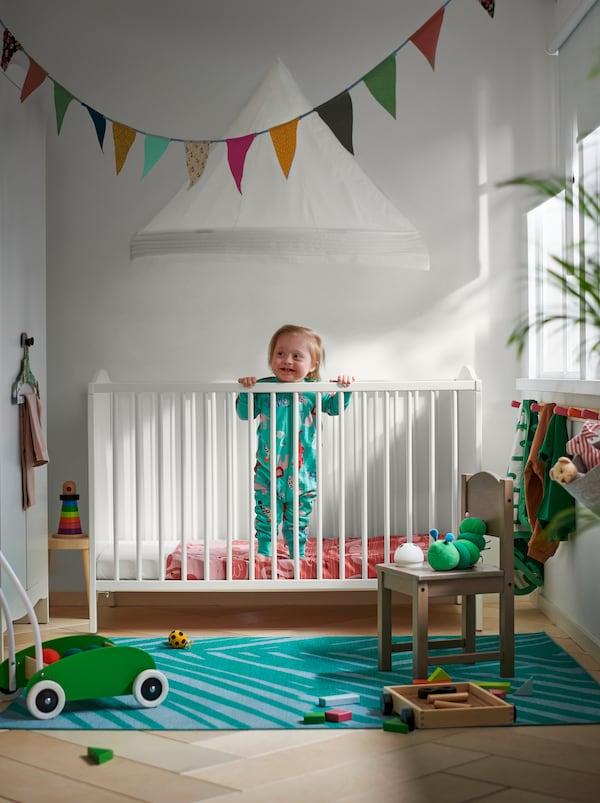 Et lille barn står op i en SMÅGÖRA tremmeseng, og rundt omkring sengen er der børnemøbler og legetøj i røde, grønne og lyseblå farver.