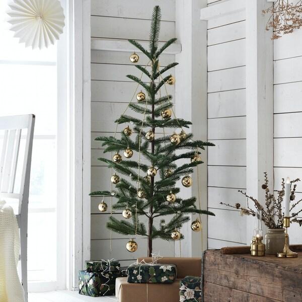 Et lille juletræ i hjørnet af en hvid træhytte.