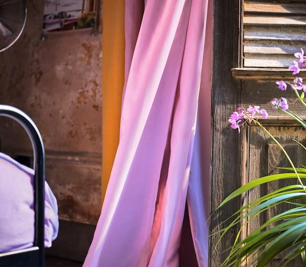 Et lyserødt gardin i en åben terrassedør.