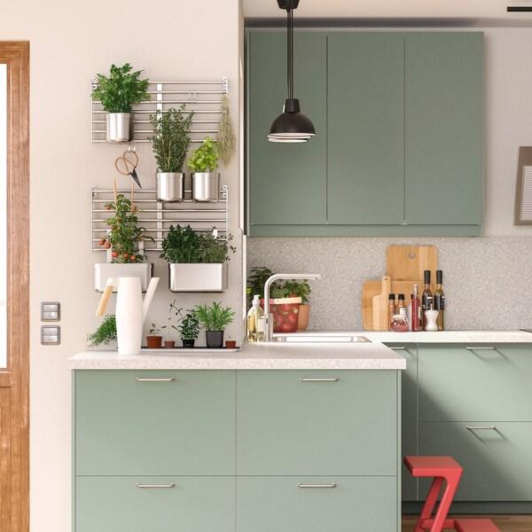 Et lyst køkken med hvid bordplade og KUNGSFORS køkkenreol.