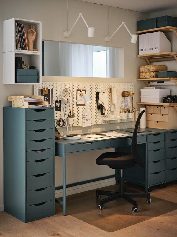 Et lyst skrivebord foran et vindue med et lyseblåt gardin foran