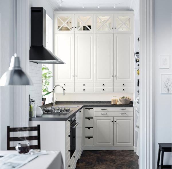 Et mindre råhvidt BODBYN køkken med vitrinelåger.