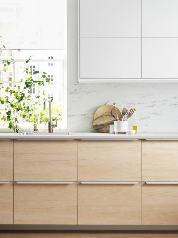 Et minimalistisk køkken med underskabe af træ og hvide overskabe.