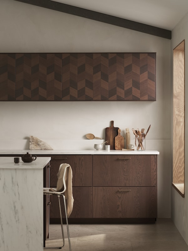 Et moderne kjøkken med SINARP skuffer, NYDALA håndtak, HASSLARP dører og ei marmormønstret kjøkkenøy.