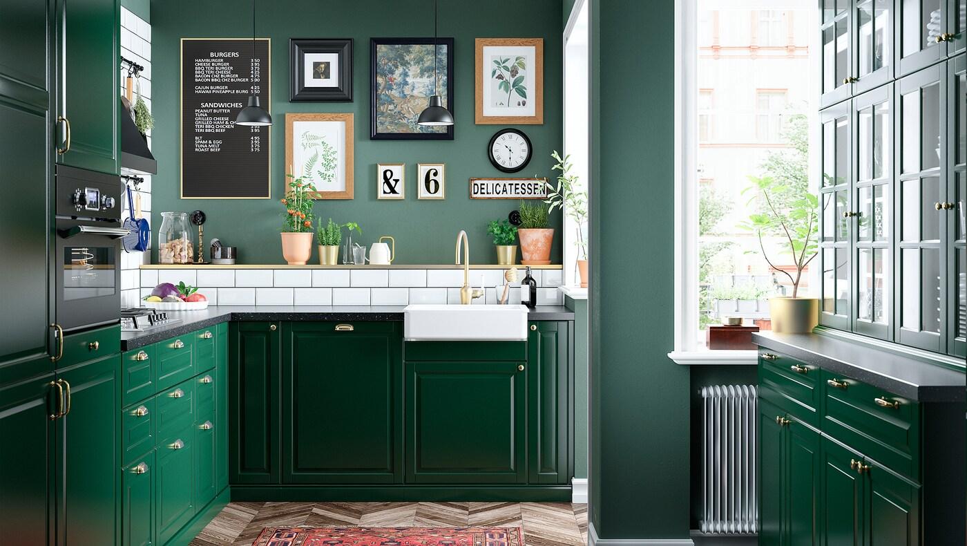 Et mørkegrønt traditionelt køkken med hvid vask.