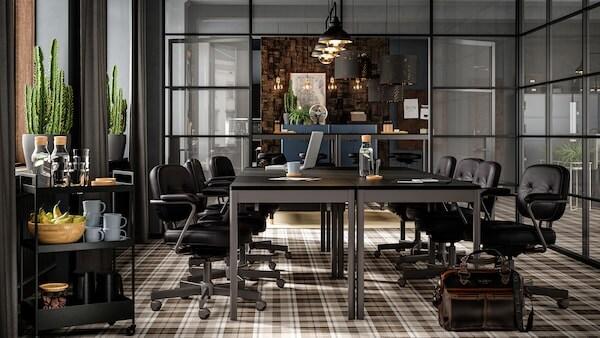 Et møterom med TOMMARYD bord satt sammen til et konferansebord i mørke farger.