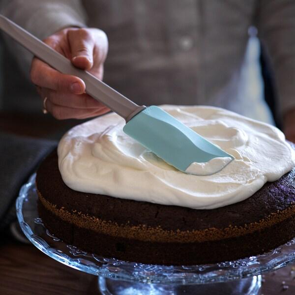 Et nærbillede af en person, der putter glasur på en kage på en piedestal med en BAKGLAD dejskraber.