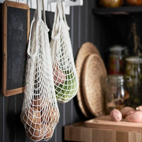 Et net med kartoler og grøntsager hæger på en krog op af en sort væg.
